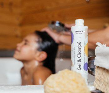 En el primer plano se ve el Gel & Champú Anainas a la derecha. En el fondo se ve una niña a la que le están lavando el pelo en una bañera.